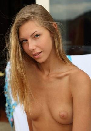 Совершеннолетняя русская модель позирует в вызывающих позах на кресле