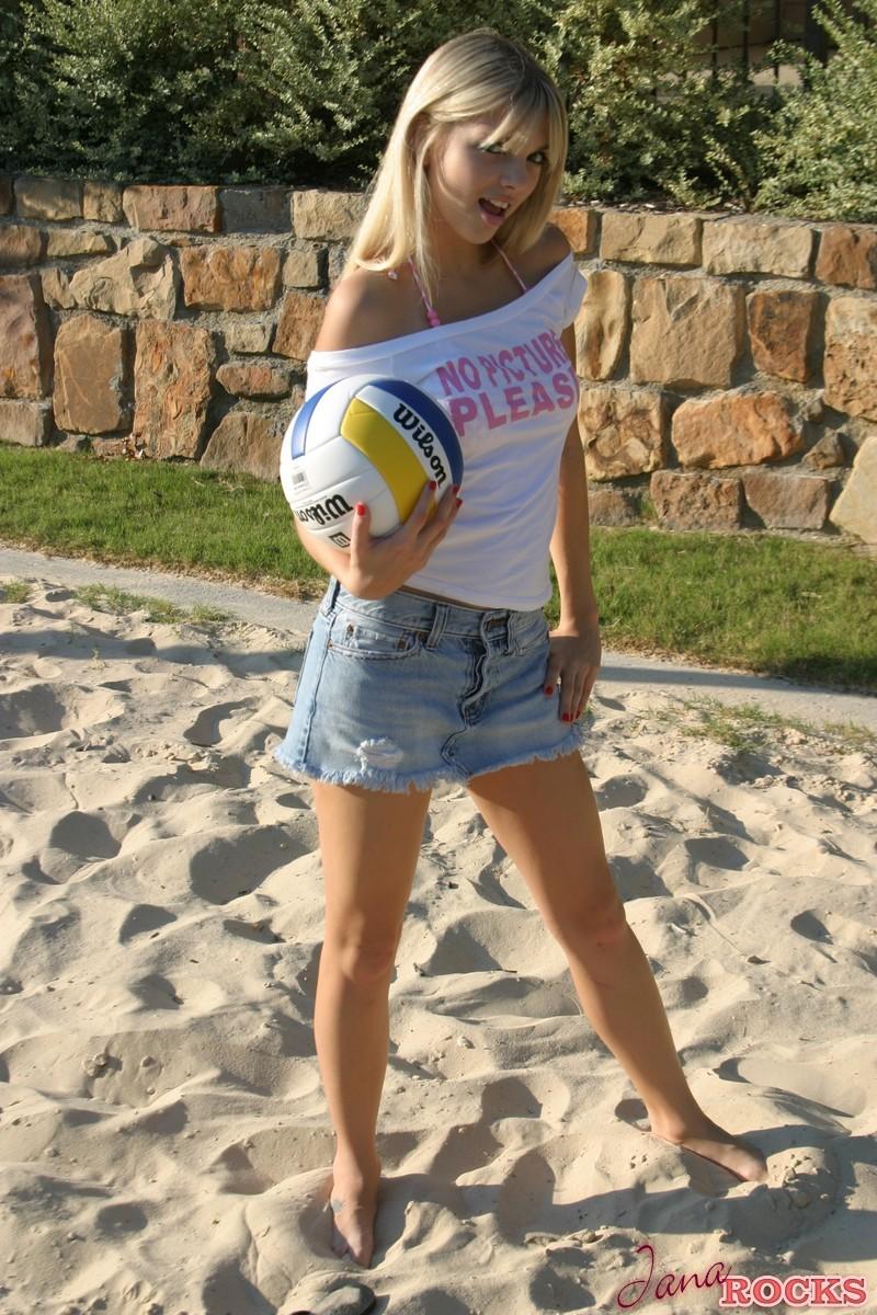 Молодая волейболистка в короткой юбке шалит на песке